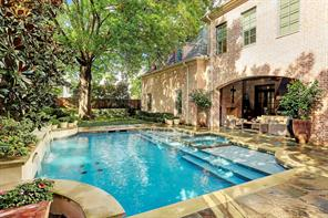 Stunning backyard with mature Magnolia trees and beautiful towering tree!  The saltwater pool is heated, has 3 fountains, 6-7 feet at its deepest point, decked with flagstone and limestone, and surrounded by lush professionally landscaped yard!