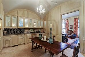 The wine room features custom painted paneled walls, limestone floors, groin vault ceiling, built in cabinets with antique mirrored upper  fronts, stone counter tops, ice maker, and wine refrigerator.  A beautiful space to have wine tasting parties!
