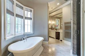 Master bathroom with Carrara marble, dual sink areas, soaking tub, walk in shower with dual shower heads, and a towel warmer!