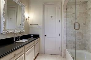 Secondary bathroom with granite counter tops, tub/shower with subway marble tile and glass shower doors.