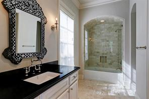 This is one of 6 ensuite bathrooms features honed granite, marble tile, tub/shower, marble subway tile, and glass doors.