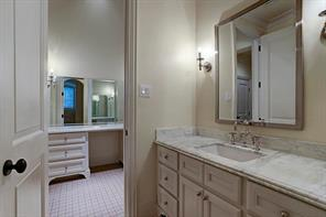 Large secondary bathroom with separate private areas.  Marble counter tops, sconces, and tons of storage complete the space.