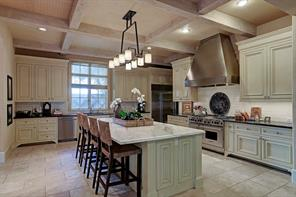 Fabulous chef s kitchen with Carrara marble island, honed granite counter tops, white French tile back splash, custom ceiling coverings, and bleached wood beams!  Stunning!