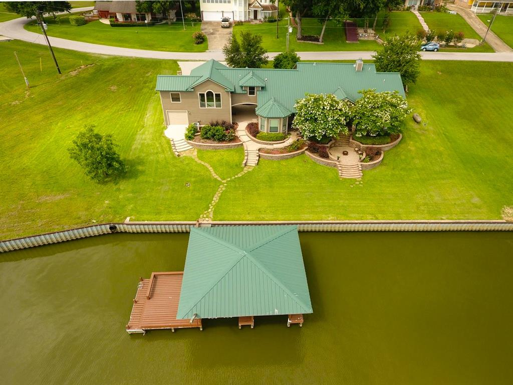 Stunning waterfront home in Coldspring Terrace on Lake Livingston. 4/3/3 with bonus room, office area, and gameroom/media room.  This tastefully decorated home boasts amazing open water views of Pine Island. Open concept living with 3 spacious bedrooms downstairs, each with en suite bathrooms.  Water views from 2 of the downstairs bedrooms & the living areas of the home.  Large utility room downstairs has built-in cabinets & a desk area that would be well suited for sewing/craft area.  Upstairs is a large game room/media room with views of the lake, an office area, large bunk room, bonus room (currently being used as a bedroom), & a half bath. Inviting outdoor spaces overlooking the lake. Large garage w/ a convenient single garage door on lake side for accessing your water toys. Boathouse has a rope swing, cradles for a boat & 2 jet ski, storage, deck, & a ladder for swimmers. Community has boat launch, fishing pier/picnic area, & pool. Resort living an hour north of downtown Houston!