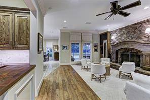 Adjacent to the DEN, is the WET BAR with its hardwood flooring, wood countertops with marble subway tile backsplash, stained wood cabinets/drawers, glass front cabinets with glass shelving, built-in wine storage shelving, under cabinet lighting and stainless ice maker.
