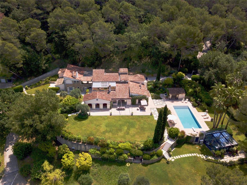 Stunning provencal residence located in quiet and residential area close to all amenities and golf course, panoramic views in all directions, including the city of Grasse, living space of 5382 sqft, south/west exposure, ground floor includes beautiful entrance with high ceiling, guest bedroom, with wardrobe and shower, large living/dining areas w/fireplace, library and home cinema, all opening into the main terrace w/arbor and pool, kitchen w/modern appliances, large master bedroom opening onto beautiful terrace, wonderful guest bedroom, additional guest/tenant house w/living rooms, kitchen, shower with opening onto 2 terraces, beautiful artist atelier with A/C, oil heating, A/C throughout residence, laundry room, superb vaulted wine cellar, phenomenal heated swimming pool, with pool house, sauna, shower, tennis court, ground for petanque boules, 6.2 acres of beautifully landscaped grounds planted with olive trees, orange trees, vines, roses, 2 wells for watering, 4 garage spaces.