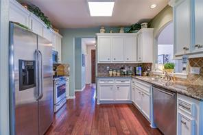 WONDERFUL KITCHEN WITH LOTS OF CABINETS FOR STORAGE. NOTICE THE STAINLESS STEEL ALLIANCES BLENDS WITH THE GRANITE COUNTERS AND CABINETS. NOT TO MENTION THE RECONSTITUTED WOOD FLOORING. REALLY LOOKS MAGNIFICENT IN PERSON