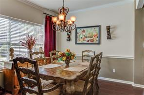 HAS FORMAL DINNING ROOM FEATURING CROWN MOLDING, CHANDELIER AND DECORATIVE DRAPES.