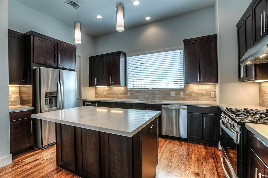 The modern kitchen features stainless steel appliances with refrigerator and wine fridge included.