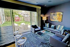 Snug room interconnects with the living room and has glass doors which provide a seamless flow to the backyard and side patios.