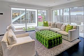 Wall of windows perfectly mesh the outdoors with the indoors in the gracious family room.