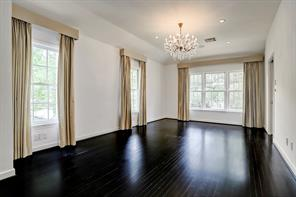 Master bedroom empowered by exquisite chandelier and recessed lighting.