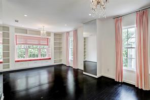 Spacious secondary bedroom complete with double chandeliers, walls of lighting, glistening hardwoods, and built ins.
