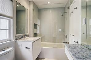 Secondary Bath with all white cabinetry, seamless glass shower door, quartz countertops and glass tile shower backsplash.