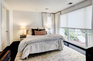 Comfortable upstairs bedroom enjoys treetop views thanks to an abundance of natural light afforded by wall of windows.  Custom shades and curtains.