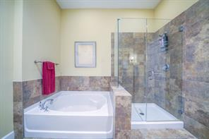 Large bathtub and walk in glass shower.