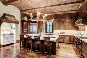 """BREAKFAST ROOM / KITCHEN: Barreled brick vaults with stained 'fir' beamed ceiling; wide plank walnut flooring; secondary staircase with wrought iron stair handrail and 1.5"""" bullnose walnut treads & risers; hidden storage under staircase."""