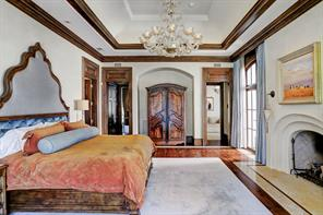 MASTER SUITE (23 X 17): Two mahogany French doors with arched paneled transoms; Venetian plaster arched wood burning / gas fireplace with Jerusalem gold slab hearth and twin custom hanging sconces; Venetian plaster faux painted walls; wide-plank walnut flooring with herringbone framed travertine; double coffered ceiling; drapery pockets with custom draperies; Murano glass custom chandelier; 20 panel mahogany framed window overlooking gardens; recessed reading lights.