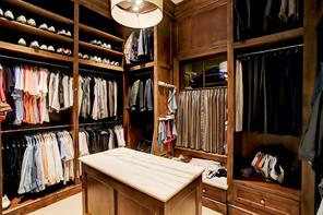 One of two MASTER CLOSETS (14 X 14): Stained Alder cabinetry; wool carpet; two chests of drawers; packing island with Calacata slab top with side opening for additional storage; glass front lighted display cases; garment rods; rotating built-in watch station, custom lighting and extra storage.