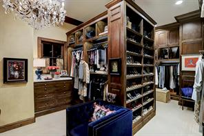 Another MASTER CLOSET: Custom built-in vanity with window for natural lighting; wool carpet; coffee station with refrigerator; three way full length mirror with storage behind mirrors; 13 pegs for belts & purses; upper level storage; glass front lighted wardrobes; shoe storage built-ins; versatile garment rods throughout; custom Alder wood woodwork, drawers & storage with marble countertops; make up table; enclosed wardrobes & storage cabinets; custom built Alder shelves for shoes, purses & belt