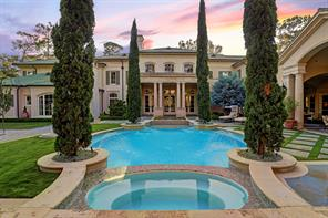 POOL / SPA: Heated pool has white plaster with glass tile and four multi directional spray fountains all framed by four towering Italian Cypress.