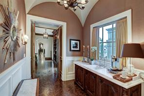 GUEST SUITE FOYER: Herrringbone walnut flooring; groin vault ceiling; wainscotin; upholstered walls, custom 8 candle chandelier; Calacata slab marble top custom built cabinet with sink with filtered water designed to house coffee / tea bar.