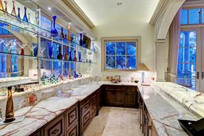 SUNKEN BAR: Carved architectural pediment frames opening to the bar; exotic Honey Onyx lighted clad bar, countertops and back splash; stainless steel under-mount sink with custom faucets; glass shelving on mirrored wall; Alder cabinetry; dishwasher and Sierra Stone honed travertine.