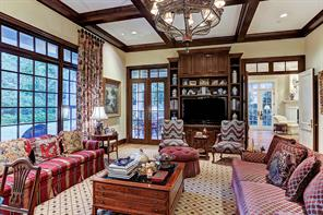 """[Den/Great Room 25'6""""x18'8""""]Spanning the rear of the house, the den/great room offers floor-to-ceiling windows overlooking the covered patio, a media/display cabinet (shown, and French doors to the patios and living room. Note coffered ceiling."""