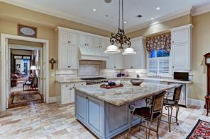 [Kitchen 18x12]The light-filled gathering kitchen has a honed travertine floor, a granite-topped island with pull-up dining ledge; and professional-grade appliances.