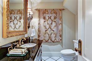 [Powder Room]Elegantly-appointed powder room has a custom sink cabinet with gold-banded porcelain sink.