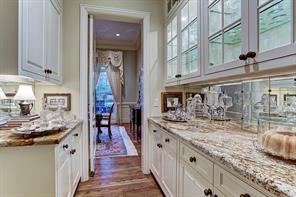 [Butler's Pantry]The butler's pantry connects the dining room and kitchen through a pivot door. Note granite countertops, French-inspired mirrored-tile backsplash with bronze studs, and abundant cabinet and drawer storage.