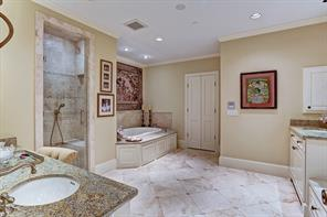 [Master Bathroom]Sumptuous master bathroom offers luxury and refinement. Separate sink cabinets; vanity; inlaid marble floor; granite countertops and air-tub deck; travertine and glass shower; window seat; under-counter refrigerator; and enclosed water closet.