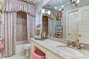 [Secondary Bedroom En Suite Bathroom]Note granite countertop, porcelain tile floor, and tub/shower with porcelain tile and inlaid stone surround.