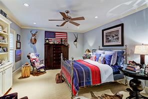"""Third En Suite Bedroom 18'7""""x14'5""""]This large bedroom features a bookcase and cabinets, sitting area, and a custom-fitted walk-in closet."""