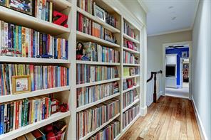 [Hallway to Game Room]Wall of bookcases form an exceptionally good use of space in this second-floor hallway leading to the return staircase, game room, and guest/fourth bedroom and bathroom..
