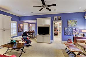 """[Game Room 22'5""""x14'1""""]Light-filled game room offers a media cabinet, abundant storage cabinets plus a holiday closet, and plenty of seating. Note entrance to an attached guest bedroom and bathroom."""