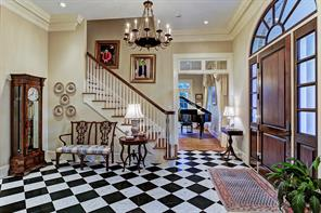 [Foyer ]Magnificent entry offers a classic black-and-white marble-tiled floor. Note sunburst transom above the front door. Opening to living room is shown at right.