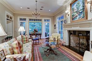 """[Formal Living 27'8""""x17'10""""]Light-filled formal living room extends from the foyer rearward to overlook the gardens and lawn. Door at left opens to the great room. Note over-sized classically-carved fireplace, floor-to-ceiling windows, and hardwood floors."""