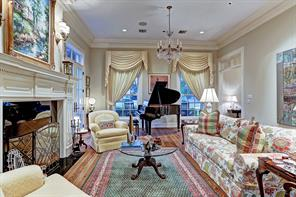 """[Formal Living 27'8""""x 17'10""""]Alternate living room view reveals the tall windows overlooking the front porch with slate hardscape, the motor court, and lawn. Note French doors at left that open to the side gardens and patio."""