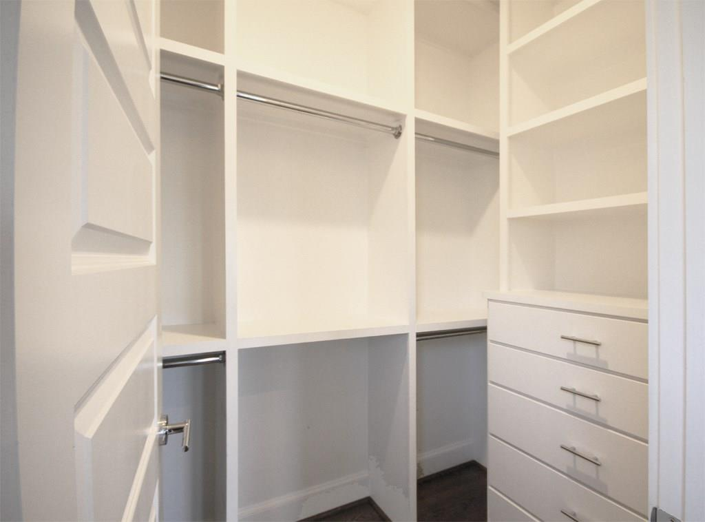 First of two master bedroom closets with built in storage