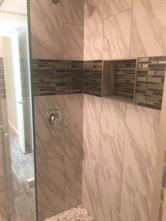 Closer look at the beautiful tile work in the shower. There is even a toiletry shelf!