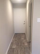 Entry door from parking area. New wood tile throughout the unit with a neutral color palate. Fresh, neutral paint throughout the unit as well.