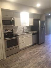Updated kitchen with granite counters, marble tile backsplash, and stainless steel appliances.