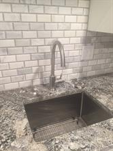 Deep, single compartment, stainless sink with new faucet and garbage disposal.