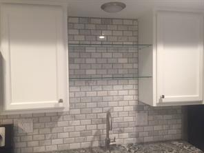 Glass shelves above sink for display or storage.