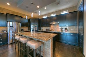 This area is for some serious cooking!! Friends and family can gather putting the chef in middle of all going on! Custom exotic granite, stainless steel appliances, custom hardware and an abundance of Espresso wood cabinets make this a most inviting area. The refrigerator also stays.
