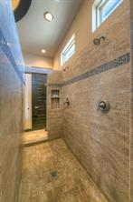 Walk-thru shower of travertine and custom glass tile trim with multiple sprays. Notice the windows above to allow natural light. The linen closet is conveniently located at the end.