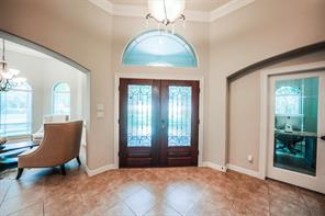 When you enter the home the study is on the left with the beveled glass French doors & built-in shelves, and the dining room is on the right with built-ins and chandelier. The tile flooring keeps it easy to clean!