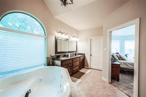 Two sinks, jetted tub, two closets, over-sized shower and water closet round-off the master bath. It also has a pretty chandelier.