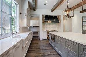 """The kitchen includes a 48"""" built-in SubZero fridge, a 6-burner gas Wolf range with a griddle and double ovens, slab marble countertops and a large island with a hand-plastered top from Segreto finishes. There is also a built-in desk with cabinets and a large walk-in pantry located off the kitchen."""